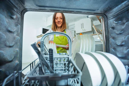 Woman take plates out of dishwashing machine