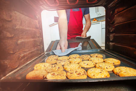 Man taking fresh baked cookies from oven with hand