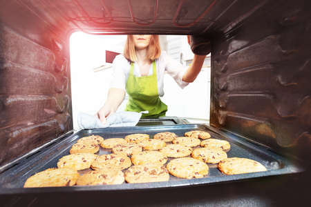 Woman open the oven to check fresh baked cookies