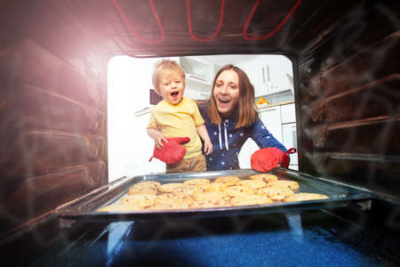 Mother and son take cookies out of oven together