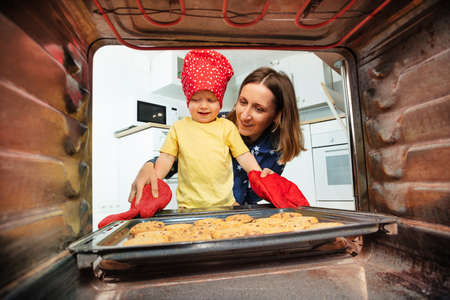 Mother and boy in chef hat take cookies from oven