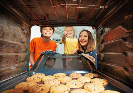 Boy point to the cookies tray in oven, with family