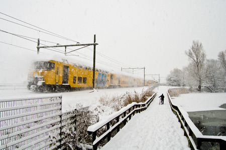 snowfalls: Train motion shot next to a bicycle bridge in one of the heaviest snowfalls in Netherlands