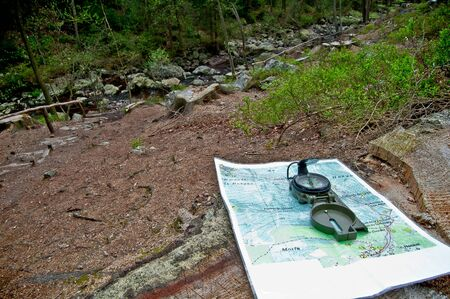 orienting: Map and compass next to an Ardennes river Stock Photo
