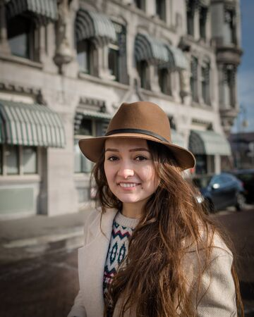 Portrait of a young woman with an elegant hat and coat. Trendy woman traveler with smile touring old town. Beautiful girl walks in Rotterdam, Netherlands.