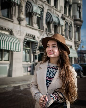 Portrait of a young woman with elegant clothes walking in the city. Trendy woman with a smile looking on buildings and touring old town. Beautiful girl exploring Rotterdam, Netherlands Stock Photo