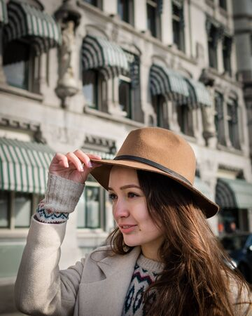 Portrait of a young woman. Trendy woman with a smile looking on buildings and touring old town. Beautiful girl walks in Rotterdam, Netherlands. Stock Photo