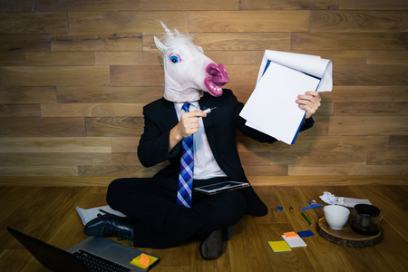 Young man in funny rubber mask sits on the floor against a wall with a lot of gadgets around him. Unicorn in a suit and tie smiles and shows a white empty sheet with copy space. Any text possible.
