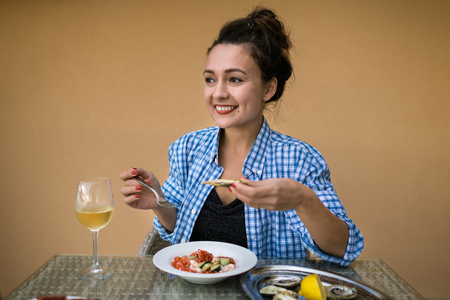 Young happy woman sits at the table with local food and glass of sparkling wine. Beautiful girl ready to eat and holds in hands oyster and fork on the background of yellow wall