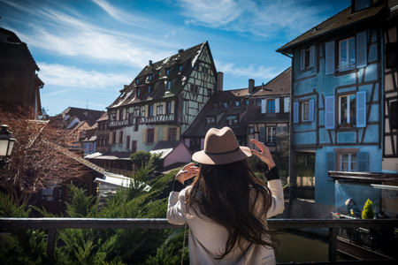 Young unrecognizable woman is standing back on the city promenade with beautiful view. Elegant female tourist explore old town in sunny day in Alsace region. Trendy traveler inspired by cityscape