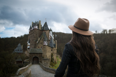 Young unrecognizable woman walks along the road leading to a incredible castle. Romantic medieval place. Sunny rays fall on the hair of elegant female traveler. Trendy girl is traveling in Europe