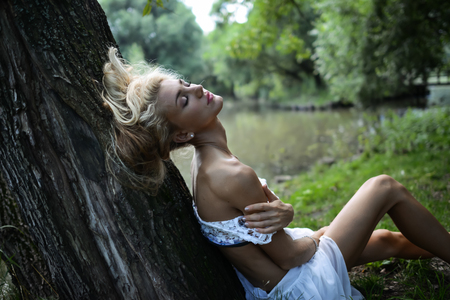 Young shapely woman sits on grass under the big tree at the riverbank in park. Slim body of blonde girl with beautiful hair in white dress on the nature background