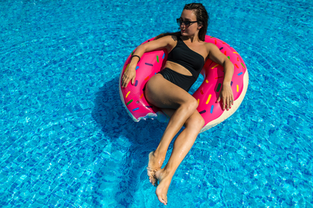 Young woman in swimwear and sunglasses lies on bright inflatable ring in the pool with blue water. Pretty girl is sunbathing in sunny day. Stock Photo