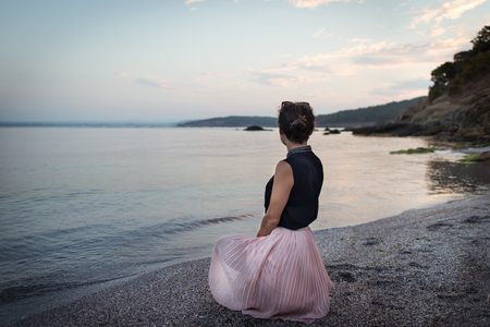 Young woman in bright dress sits on the beach and looking on the seascape. Stylish girl enjoys vacation in the evening outdoor.