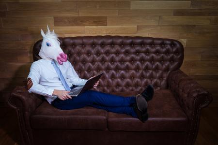 Insolito uomo che lavora in ufficio a casa. Freaky giovane manager in maschera comica sullo sfondo della parete in legno. Unicorno divertente in vestito si siede sul divano come un capo.