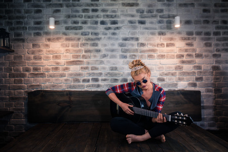 Pretty blonde girl in causal clothes playing music on guitar and singing in stylish apartment. Unusual young woman spend time at modern home.