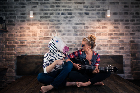 Beautiful blonde girl in causal clothes playing music on guitar for freaky man in comical mask. Unusual couple spend time together in stylish apartment. Unicorn with girlfriend at home