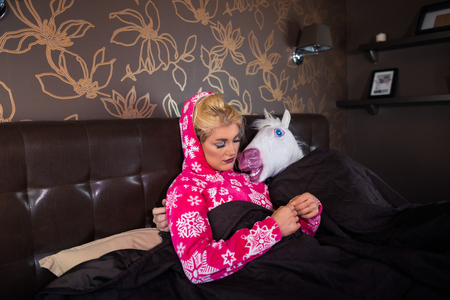 Serious girl in pajama is lying on the bed with strange boyfriend in comical mask. Unusual couple spends time together in bedroom at the stylish apartment.