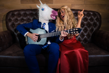 Young man in elegant suit and comical mask playing music on the guitar for funny girl in red dress. Unusual couple spend time together on a leather sofa in stylish apartment. Unicorn with girlfriend