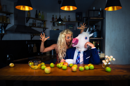 Unusual couple spend time together at the bar counter in stylish apartments with food and drinks. Funny girl scared strange boyfriend in comical mask. Unicorn in suit with young woman Stock Photo