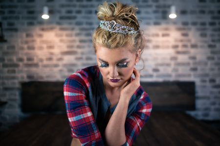 Attractive young woman sits on bed in stylish bedroom. Russian blonde girl in crown and casual clothes sad alone in modern apartment with soft light.