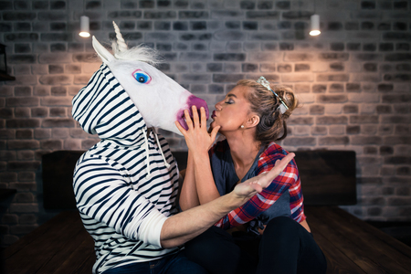 Happy young woman embraces with funny man in comical mask and sits on the bed in stylish apartment. Blonde girl with boyfriend in bedroom. Unusual couple celebrates housewarming.