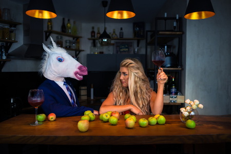 Unusual couple spend time together at the bar counter in stylish apartments with wine and food. Beautiful girl relaxing with funny boyfriend in comical mask. Unicorn in suit with young woman