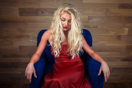 Young blonde woman sits on armchair. Pensive girl in elegant red dress posing on camera on background of wooden wall.