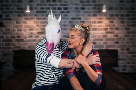 Unusual couple celebrates housewarming. Happy young woman with funny man in comical mask sits on the bed in stylish apartment. Blonde girl with boyfriend in bedroom.