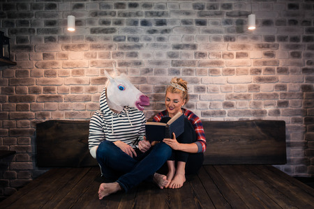 Unusual couple reading a book in stylish apartment. Beautiful girl sits on bed with funny man in comical mask. Young woman with freaky boyfriend at home. Stock Photo