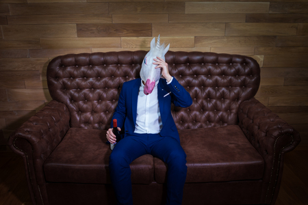 Funny unicorn in elegant suit sits on sofa with bottle of wine. Unusual boss with headache at home. Freaky man in comical mask on background of wooden wall.