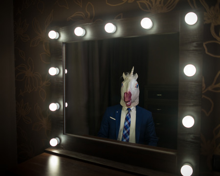 Glamour guy in suit and mask looks at himself in the mirror in dressing room. Freaky young man in stylish room posing like a boss. Unusual unicorn.