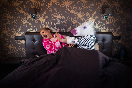 Angry man in comical mask fighting with scared girlfriend in pajama on the bed. Unusual couple find out relationship problems in stylish bedroom.