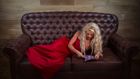 Blonde girl lies on leather sofa and looking old photos. Young woman in red dress relaxing in stylish room on background of wooden wall.