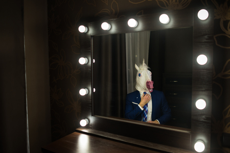 Glamour man in elegant suit and funny mask corrects tie and looks at himself in mirror in dressing room. Freaky guy posing like boss. Unusual unicorn. Stock Photo