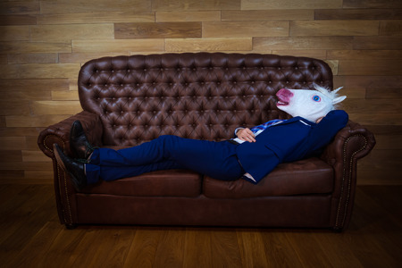 Funny unicorn in elegant suit lies on leather sofa. Unusual man relaxing at home. Freaky guy in comical mask on background of wooden wall.