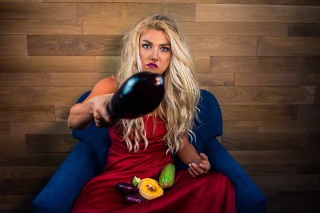 Young funny woman in elegant red dress sits on armchair near wooden wall and holds vegetables in hands. Unusual housewife gesticulating. Фото со стока - 121910036