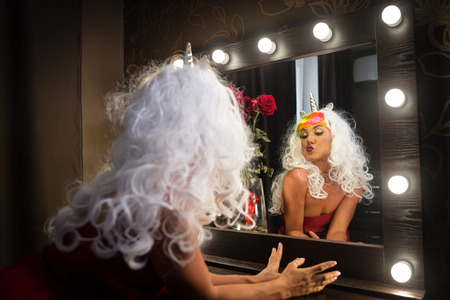 Freaky young woman in unusual wig looking at himself in mirror in dressing room with flower. Strange lady in red dress. Funny girl unicorn makes faces