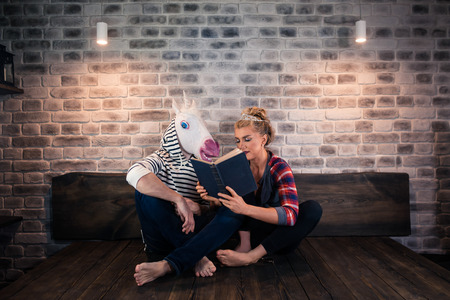 Unusual couple reading a book in stylish room. Beautiful girl sits on bed with funny boyfriend in comical mask. Young woman with freaky man. Stock Photo