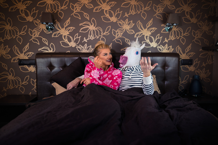 Beautiful young woman in pajama lying on the bed with funny boyfriend in comical mask and dreaming. Unusual couple at the stylish bedroom. Stock Photo