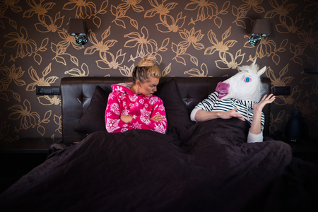 Serious girl in pajama sits on bed with strange boyfriend in freaky mask. Relationship problems of unusual couple. Young woman with unicorn. Stock Photo