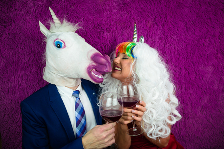 Portrait of strange couple on purple background. Freaky young woman in unusual wig drinking wine with man in mask and suit. Unicorn with girlfriend.