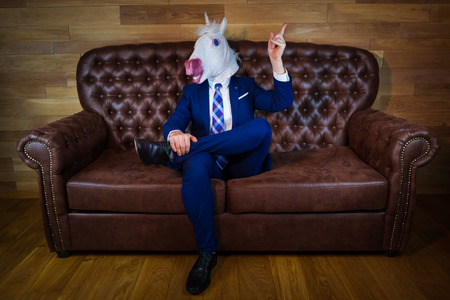 Funny unicorn in elegant suit siting on sofa like a boss and showing hand gesture with raised index finger. Unusual man at home. Freaky guy in mask.