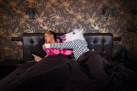 Freaky man in unicorn mask molest to scared girlfriend in pajama in bed. Unusual couple has relationship problems in stylish apartments.