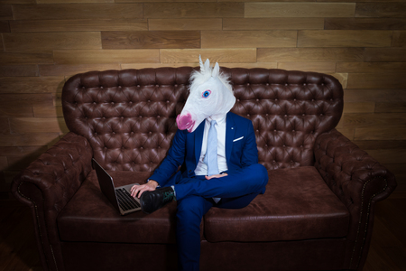 Strange guy in elegant suit working in home office. Unusual young man in mask on background of wooden wall. Funny unicorn sits on sofa like a boss.