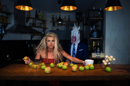 Unusual couple at bar counter in stylish kitchen with apples and tea. Funny girl eating apple with boyfriend in mask. Unicorn in suit with young woman