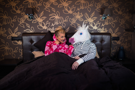Young woman in pajama sits on bed and talks with funny boyfriend in comical unicorn mask. Unusual couple spends time together in stylish bedroom.