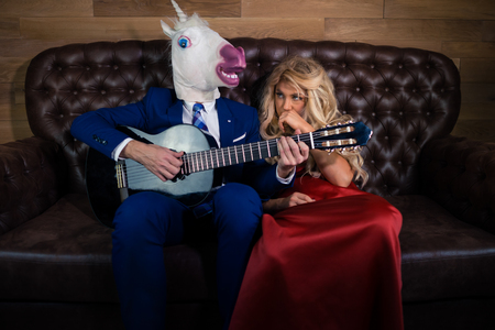 Man in suit and mask playing music on guitar for sensual girl in red dress. Unusual couple on leather sofa in stylish room. Unicorn with young woman