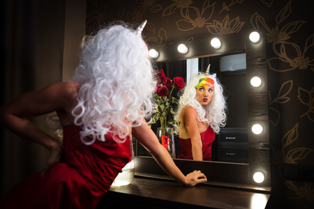 Funny young woman in unusual wig looking at himself in mirror in dressing room with flowers. Strange lady in red dress. Girl unicorn makes faces.