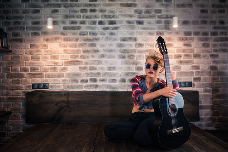 Freaky blonde girl in causal clothes sits on bed with guitar in stylish apartment. Glamour young woman spend time at modern room.